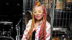Vicky Österberg med färglada dreadlocks framför trummor.