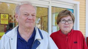 En man och en kvinna står utanför en matbutik.