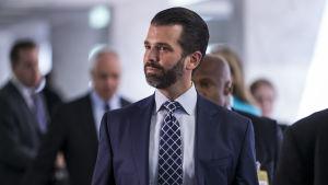 Donald Trump jr i kostym, med skägg, på väg in på slutet kongressförhör.