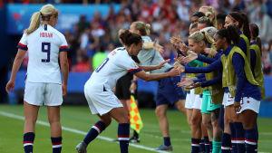 Carli Lloyd firar ett mål med lagkamrater.