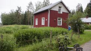 Ett rött hus på landsbygden med en rullator i förgrunden.