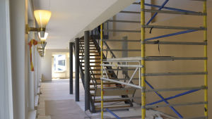 en trappa som leder upp till övre våningen med en byggnadsställning framför