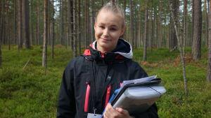 Janni Heikkinen med svart jacka, namnskylt och mappar i handen. En tallskog i bakgrunden.