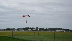 En fallskärmshoppare går ner för landning på ett grönt fält. I bakgrunden syns flyghangarer.
