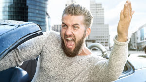 Mies autossa nostaa käsivarttaan ylös huutaen.