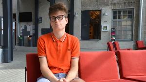 En ung man sitter på en röd soffa.