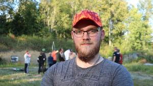 En man med röd keps och glasögon står med armarna i kors.