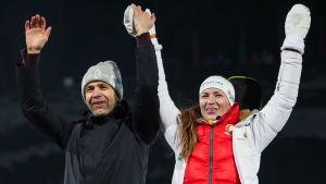 Ole Einar Björndalen och Darja Domratjeva sträcker upp armarna i luften