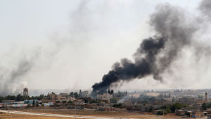 En brinnande by i kurdkontrollerade områden. Byn ses på långt håll och det reser sig svart rök från byns centrum.