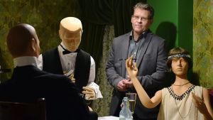 Dan Lindholm står bredvid tre dockor som sitter vid ett bord. Den ena dockan har en spritplunta i fickan.