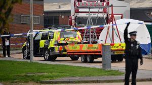En polisbil med en släpvagn parkerad framför en lastbil. Området är avspärrad med polistejp, en uniformbeklädd polis står framför.
