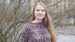 En ung kvinna står framför ett syrenbuskage.