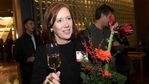 Sirpa Paatero (SDP) med skumpaglas och blommor i handen.