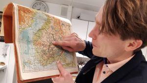 Blivande skogsägaren Jussi Karhunen pekar med fingret på Finlnads karta och platsen där hans familjs skog ligger.