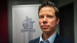 Mikko Cantell från polisens lotteriförvaltning har på sig en kostym och tittar in i kameran. I bakgrunden syns polisens vapen.