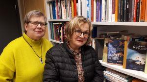 Mia Österlund och Pia Maria Ahlbäck vid barnbokshyllan.