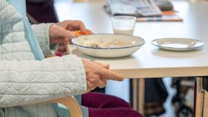 Vanhus ruokailee aamiaista.
