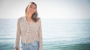 Kvinna står på en strand och ler mot kameran.