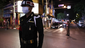 En polis i Bangkok övervakar det nattliga utegångsförbudet i staden