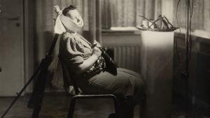 Lavastettu kuva 1920-1930-luvulta, jossa nainen istuu tuolissa ja kärsii hammassärystä.