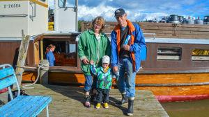 En dam, en man och ett litet barn står på en brygga utanför en större motorbåt.