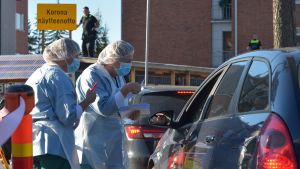 Sjuvårdspersonal i skyddsutrustning står intill en parkerad bil med fönstret nere. Coronaprover tas i Jyväskylä.