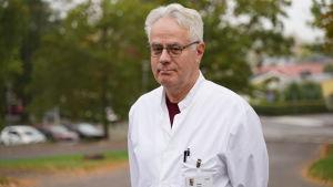 En äldre läkare i vit läkarrock står ute. I bakgrunden kan man skymta en parkeringsplats med några bilar.