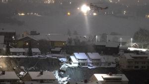 En helikopter lyser på hus som drabbats av jordskredet.