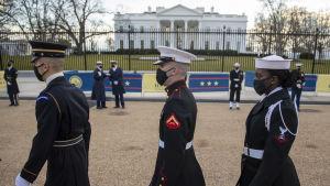 Tre personer i USA:s armétruppers paraduniform marcherar förbi kameran. I bakgrunden syns vita huset. Det är två vita män och en svart kvinna på bilden.
