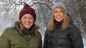 Kaksi hymyilevää naista talvimaisemassa