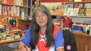 Leung Kwok-hung med långt hår sitter vid sitt skrivbord.