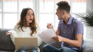 Ung kvinna och man sitter i soffa med laptop och ser irriterade ut