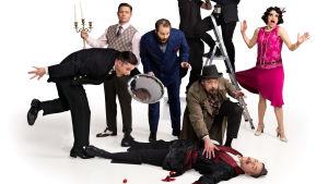 Sju skådespelare står kring en liggande kropp i humoristiska poser mot en vit bakgrund.