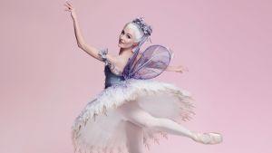 Ballerina taikasauva kädessään vaaleanpunertavaa taustaa vasten.