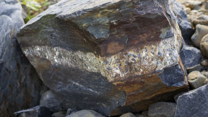 Tumma kivi, jonka keskiosassa kimaltelee vaaleampaa kiviainesta.