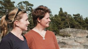 Opettaja Christiane Ala-Nissilä ja suojelubiologi Heidi Arponen seisovat Dalkär-saaren rannassa.