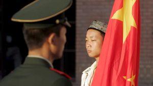 En polis och en man från uigurbefolkningen står mitt emot varandra bredvid den kinesiska flaggan