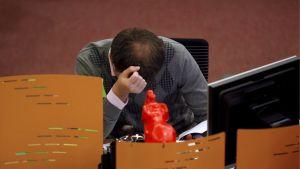 En rysk börsmäklare lutar huvudet i händerna