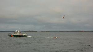 Sjöbevakningens helikopter kommer för att hämta den nödställde.