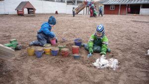 Plasthinkar fyllda med sand, barnhänder som fyller på mera sand.