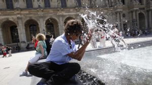 Kvinna svalkar sig utanför Louvren i Paris