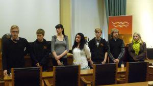 Ungdomsfullmäktige har tillsatt en styrelse. Den består av fr.v ordförande Henrik Hurtig, Osku Hurtig, Saana Hautala, Sini Tullila, Ville Myllyaho och Tuure Vairio. Milja Ångerman saknas på bilden. Till höger Anne-Mari Pipatti, koordinator för ungdomsären