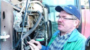 Jordbrukaren Erik Oljemark granskar sin traktormotor