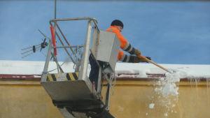 En man kastar ner snö från tak