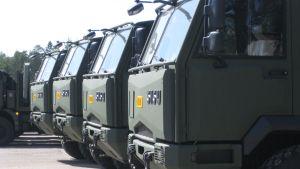 Militära Sisu-lastbilar i rad på fabrikens gårdsplan i Karis.