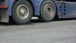Lasbil kör på ett brunnslock