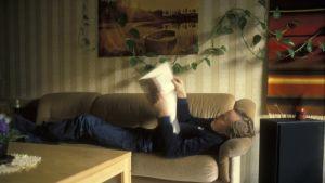 Man ligger i soffan och läser en tidning