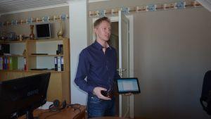 Tim Wallin håller i en telefon och en surfplatta.