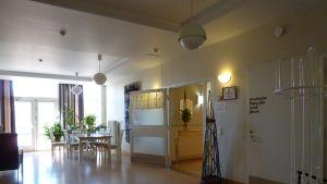 Ingången till vårdavdelningar på Mjölbolsta i Karis. Matbordsmöblemang, öppne dörr, stort ljust fönster.