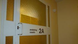 Dörren till en avdelning i sjukhusfastigheten i Mjölbolsta. Lapp uppmanar att hålla dörren stängd.
